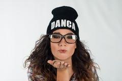 送打击亲吻的行家帽子的年轻舞蹈家女孩 免版税图库摄影