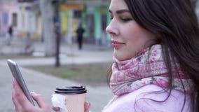 送消息、妇女有手机的和杯咖啡坐的互联网街道特写镜头的 股票视频