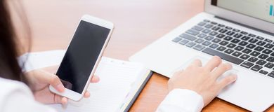 送电子邮件联络的特写镜头横幅网站亚裔妇女 姿态手指按送出流动巧妙的电话和膝上型计算机 库存照片