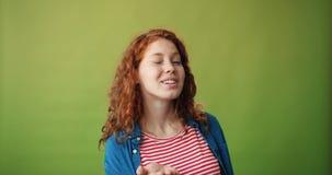 送空气亲吻和闪光在绿色背景的十几岁的女孩画象 影视素材
