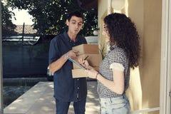 送货人家门廊把卷曲的妇女装箱 免版税图库摄影