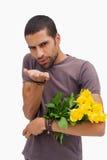 送飞吻和拿着玫瑰的英俊的人 免版税库存照片