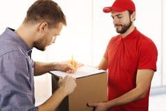 送货业务-供以人员箱子的签署的交付收据 库存图片