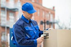 送货人扫描有条形码扫描器的纸板箱 免版税库存照片
