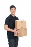 送货员在工作。拿着箱子st的快乐的年轻送货员 免版税库存图片