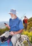 送sms的老背包徒步旅行者坐岩石 免版税库存照片