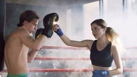 适合与男性教练的妇女训练在拳击台 影视素材