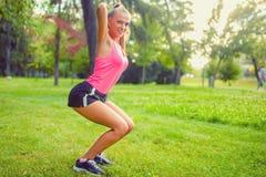 适合和肌肉妇女在公园,做蹲坐和赛跑 免版税库存照片