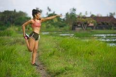 适合和运动的赛跑者亚裔妇女舒展腿的和身体在绿色领域美好的背景的连续锻炼以后在体育火车 库存照片