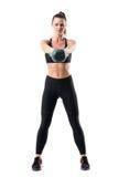 适合女运动员正面图做kettlebell在空中行动的摇摆锻炼 免版税库存照片