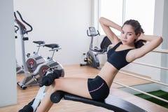 年轻适合妇女在健身屋子里坐直 库存图片