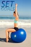 适合妇女的一个综合图象坐锻炼球在舒展胳膊的海滩 免版税图库摄影