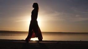 适合妇女的剪影在水附近的展开瑜伽席子,准备做瑜伽或pilates 日落海滩 影视素材