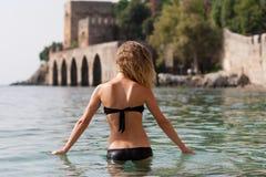 适合白肤金发的女性Backview画象站立在阿拉尼亚中世纪造船厂前面的海的游泳衣的 图库摄影