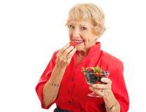 适合的健康资深夫人Eating Berries 库存图片