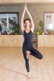 适合的女子实践的瑜伽锻炼告诉了Tree站立在一条腿的Pose户内 免版税库存图片
