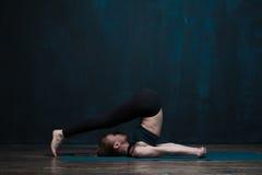 适合的女孩实践的瑜伽asana对黑暗的墙壁 免版税图库摄影