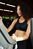 适合的女孩感人的踏车屏幕,当行使在健身房时 免版税库存照片