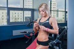 适合的女孩摆在与在健身房的手机在黑色短裤和黑上面 免版税库存照片