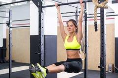 适合的女孩训练吸收通过举在一个horisontal酒吧的腿 健身做锻炼的妇女锻炼在健身房 图库摄影