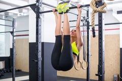 适合的女孩训练吸收通过举在一个horisontal酒吧的腿 健身做锻炼的妇女锻炼在健身房 免版税图库摄影