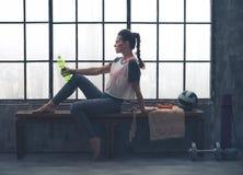 适合的妇女坐在拿着水瓶的顶楼健身房的长凳 免版税库存照片