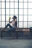 适合的妇女坐在顶楼健身房饮用水的长凳 库存照片