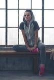 适合的妇女坐顶楼倾斜反对弯的腿的健身房长凳 免版税库存照片