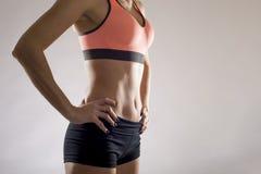适合的妇女显示微小的美丽的胃和吸收的佩带的短裤和体育上面 免版税库存图片