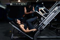 适合的妇女解决与教练员的在健身房,做肌肉训练的妇女在健身房 解决在健身房的运动员通过拉扯w 免版税库存图片
