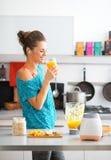 适合的妇女饮用的南瓜圆滑的人在厨房里 库存图片