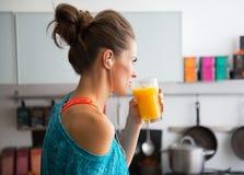 适合的妇女饮用的南瓜圆滑的人在厨房里 图库摄影