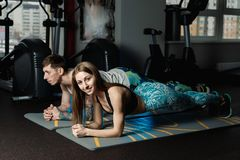 适合的嬉戏做板条核心锻炼训练后面和新闻肌肉概念健身房体育运动员健身的男人和妇女 免版税库存照片
