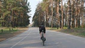 适合的嬉戏骑自行车者短跑艰难在马鞍外面 在路自行车的训练 后部跟随射击 股票录像