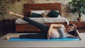 适合的孕妇举她的说谎在做体育锻炼的卧室地板上的瑜伽席子的腿 健康生活方式 股票录像