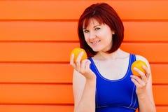 适合的微笑的年轻女人用两个桔子对色的墙壁 生气勃勃、妇女健康和健康概念 夏令时 免版税库存照片