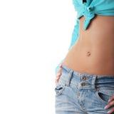适合的牛仔裤赤裸性感的胃妇女 免版税库存照片