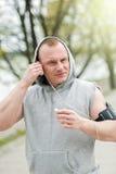 适合的由耳机的人慢跑者听的音乐 库存照片