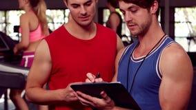 适合的男性教练员讲话与一个肌肉人 股票录像