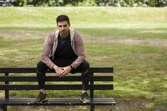 适合的年轻人坐长凳在公园 库存照片