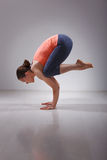 适合的yogini妇女实践瑜伽asana Bakasana 免版税库存图片