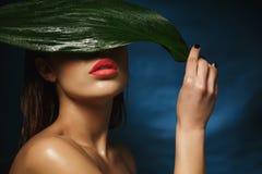 适合赤裸妇女特写镜头掩藏在大湿叶子下的 免版税图库摄影