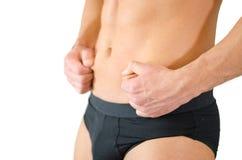 捏他的腹部皮肤的适合的年轻人 免版税库存照片