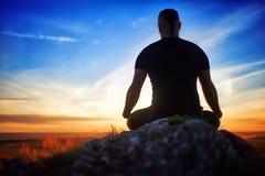 适合年轻人思考的瑜伽的背面图在莲花姿势的在美好的日落的岩石 免版税库存照片