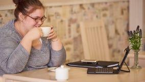 适度地坐在咖啡馆的肥胖女实业家,当拿着咖啡时 免版税库存照片