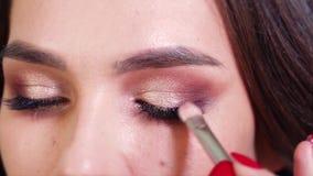 适用于发光的眼影膏的手特写镜头在慢动作的年轻女人眼皮 股票视频