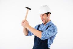 适用于发嗡嗡声的东西的滑稽的年轻建造者他的在盔甲的头 免版税库存照片