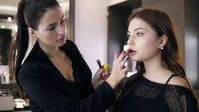 适用于嘴唇凤仙花或明亮的唇膏的白种人女性化妆师她的更低的嘴唇 侧视图 股票录像