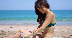 适用于太阳奶油的少妇她的腿 库存照片