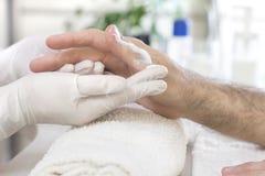 适用于奶油由一名美容师的人的手橡胶手套的 在发廊的修指甲治疗 库存照片